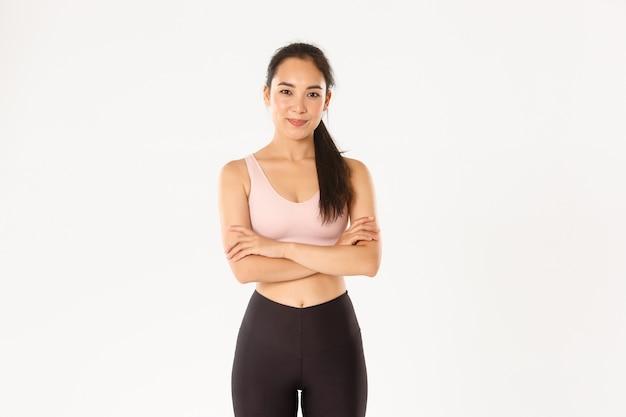 自信を持ってやる気のあるアジアのスポーツウーマンは、トレーニングの準備ができており、腕を組んで胸を組んで、生産的なトレーニング、白い背景に笑顔を奨励しています。
