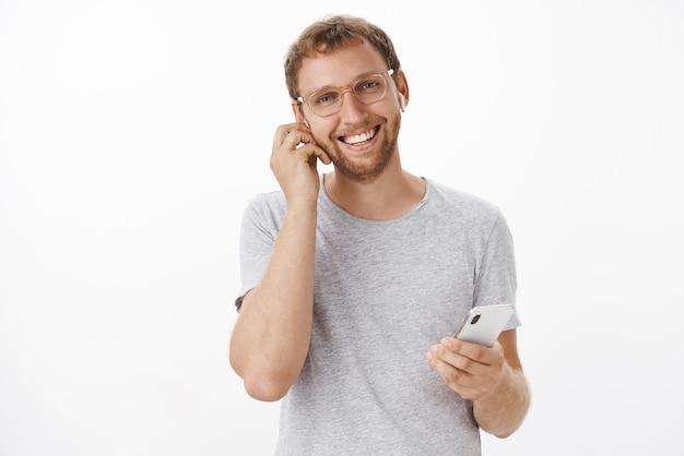 스마트 폰을 들고 무선 이어폰으로 고객과 이야기하고 친절하고 즐거운 미소를 지으며 고가의 거래에 서명하는 자신감 있고 즐거운 유럽 남자