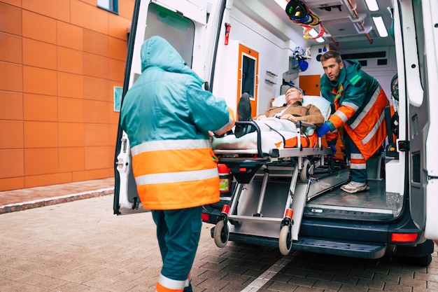 Уверенные и профессиональные врачи выгружают больного из машины скорой помощи на носилках возле здания больницы