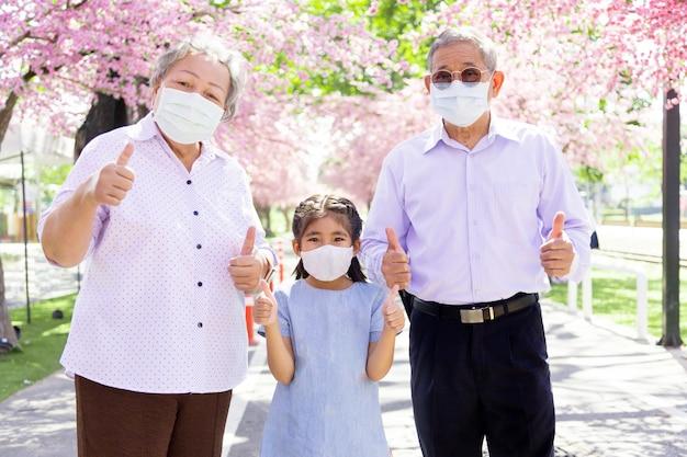 아시아 가족과 함께 야외 공원에서 자신감을 갖고 보호하십시오. 행복 할아버지와 할머니와 아이는 코로나 바이러스 전염병을 보호하기 위해 얼굴 마스크가 있습니다.
