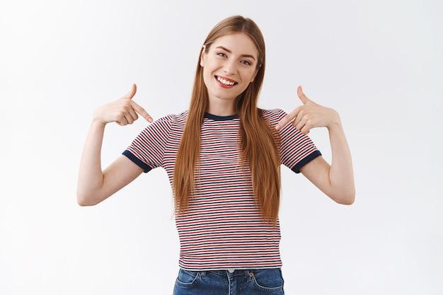 自信を持って誇りに思っている、自慢の美しい女性がストライプのtシャツを着て、自信を持って笑顔で頭を傾け、カメラを注視して、自分の成果を促進し、自慢している白い背景を指しています