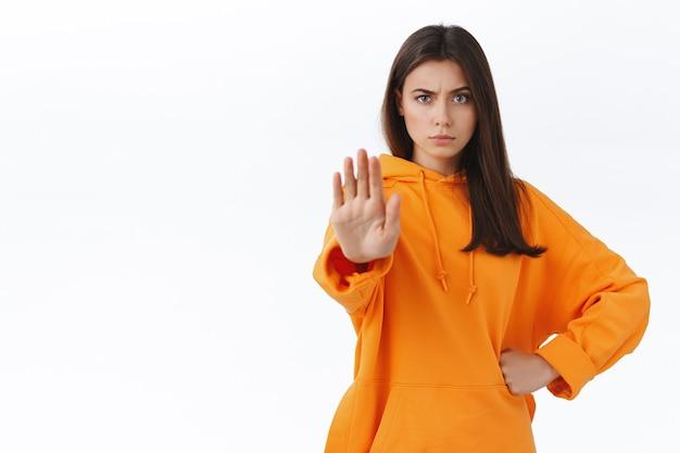 Уверенная и серьезная женщина требует остановки, приказывает прекратить это, не хмурится и смотрит в камеру решительно, вытягивает руку вперед в жесте остановки, не нравится и не согласен с вами, белая стена