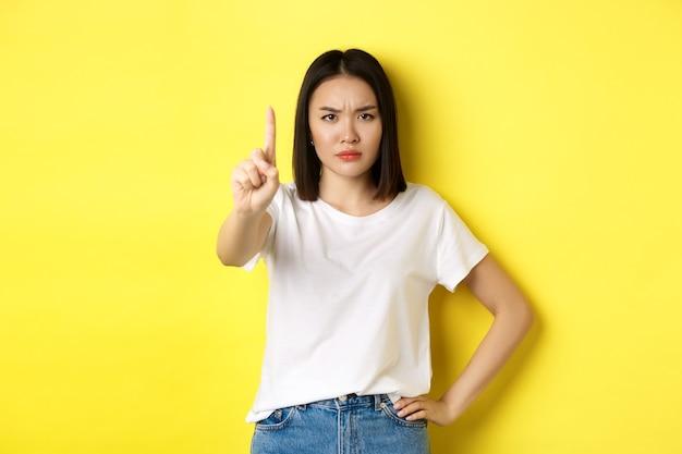 Уверенная и серьезная женщина говорит «нет», показывает протянутым пальцем, чтобы остановить и запретить что-то плохое, хмурится и уверенно смотрит в камеру, стоя на желтом фоне.