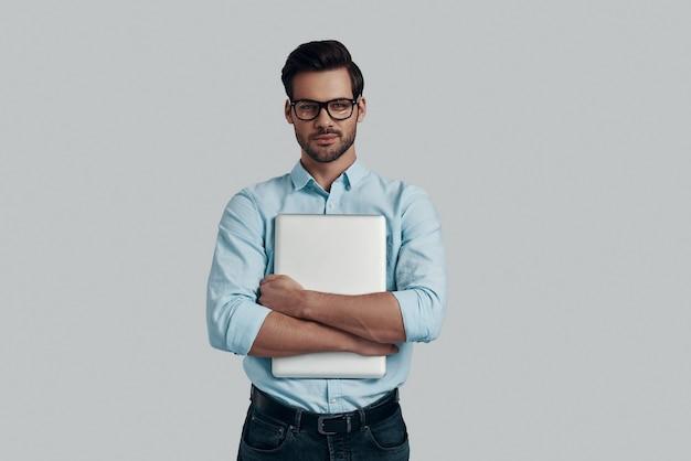 自信を持って賢い。ラップトップを携帯し、灰色の背景に立って笑っているハンサムな若い男