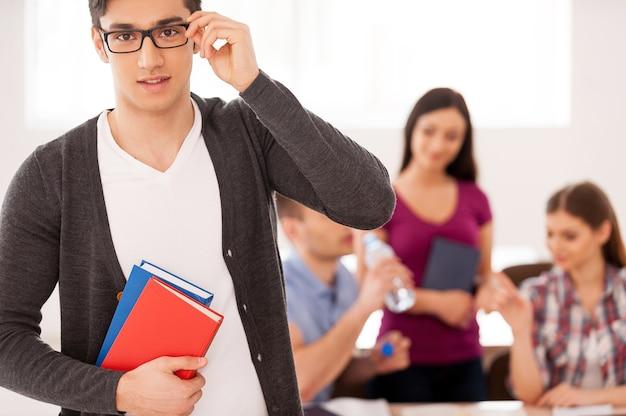 自信を持って賢い学生。他の学生が背景に座っている間、本を持って眼鏡を調整する自信のある男子生徒
