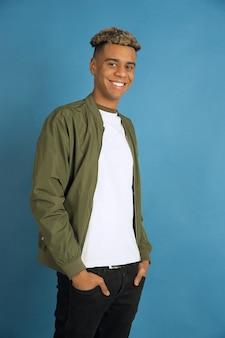 자신감과 미소. 블루 스튜디오 배경에 고립 된 아프리카 계 미국인 남자의 초상화. 캐주얼 옷에 아름 다운 남성 모델입니다. 인간의 감정, 표정, 판매, 광고의 개념. copyspace.