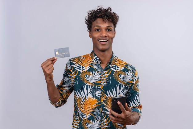 葉っぱに巻き毛のある自信と笑顔のかっこいい黒肌の男性が携帯電話を持ちながらクレジットカードを示すプリントシャツを葉っぱに
