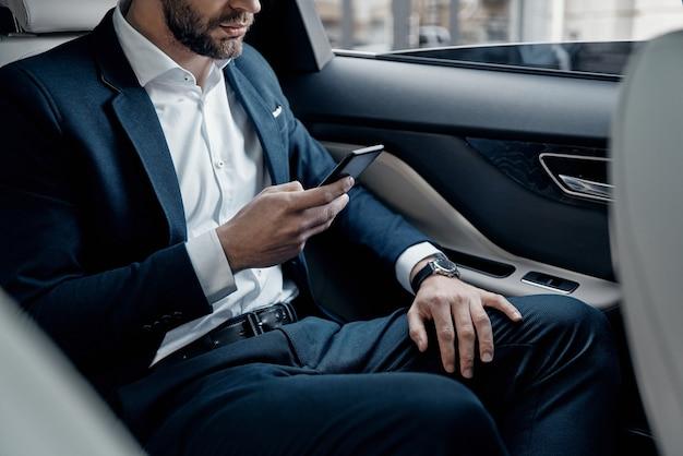 자신감 있고 성공적입니다. 차에 앉아있는 동안 스마트 폰을 들고 정장을 입은 젊은 남자의 클로즈업