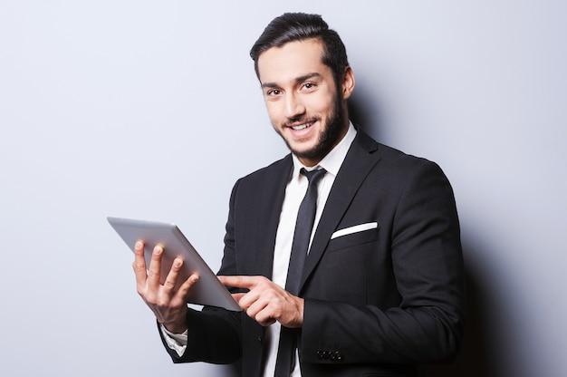 Уверенно и успешно. уверенный молодой человек в формальной одежде работает на цифровом планшете и улыбается, стоя на сером фоне