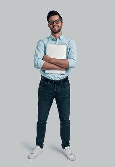 自信を持って成功しました。ラップトップを携帯し、灰色の背景に立ってカメラを見ている若い男の全長