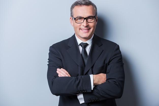 Уверенно и успешно. портрет уверенного в себе зрелого мужчины в строгой одежде и очках, смотрящего в камеру и улыбающегося, стоя на сером фоне