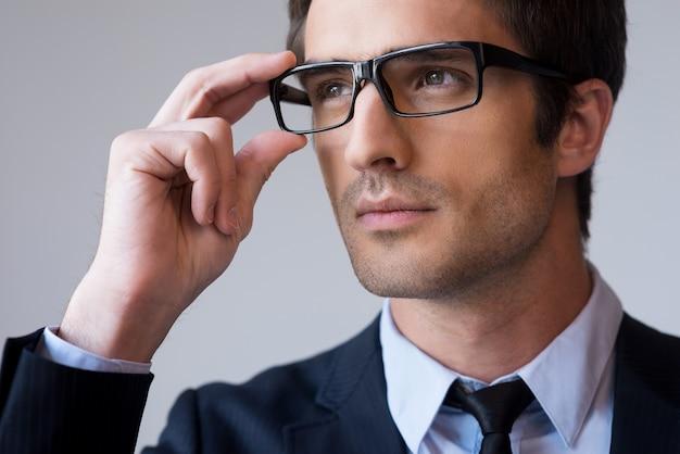 Уверенно и успешно. портрет уверенного в себе молодого человека в строгой одежде, поправляя очки