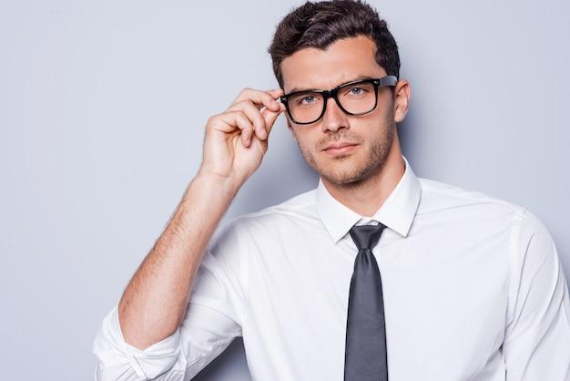 Уверенно и успешно. портрет красивого молодого человека в рубашке и галстуке, поправляющего очки и смотрящего в камеру, стоя на сером фоне