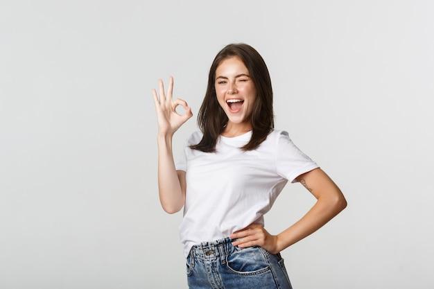 承認で親指を立てるジェスチャーを示す自信を持って明るい魅力的な女の子。