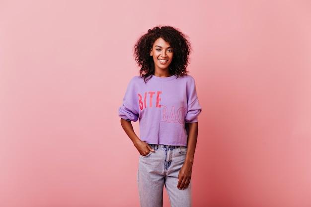 주머니에 손 을와 서 자신감이 매력적인 소녀. 보라색 셔츠에 수줍은 아프리카 여자의 스튜디오 초상화.