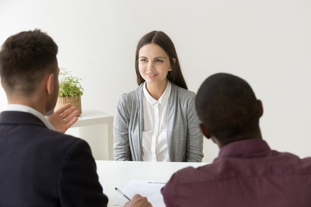 Confident applicant smiling at job interview with diverse hr managers
