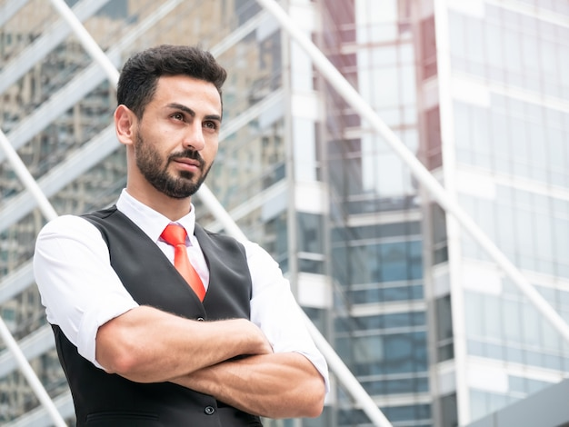 Confident arab businessman manager standing with arms crossed outdoor at front modern office.
