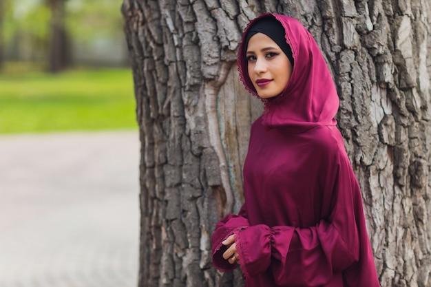 自信を持ってアラブのビジネスマンが笑顔でドバイのアラブビジネスの散歩vumenヒジャーブはドバイの高層ビルに対して通りにあります女性は黒いアバヤに身を包んだ