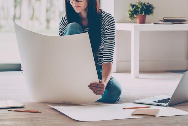 자신감 넘치는 건축가. 집에서 바닥에 앉아 있는 동안 청사진을 검사하는 자신감 있는 젊은 아름다운 여성의 클로즈업