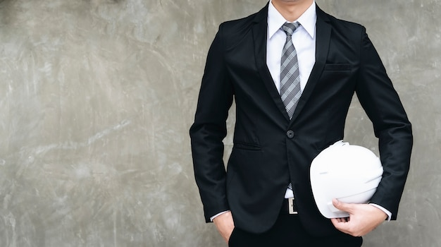 Confident architect holding a white safety hat on a cement background.
