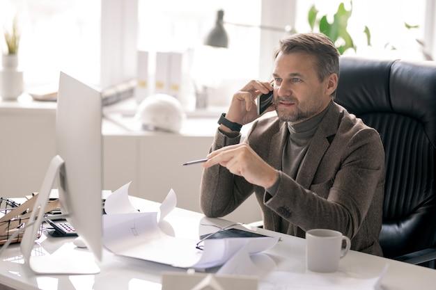 職場でコンピューターの画面を指しながら電話で話している正装で自信のある建築家