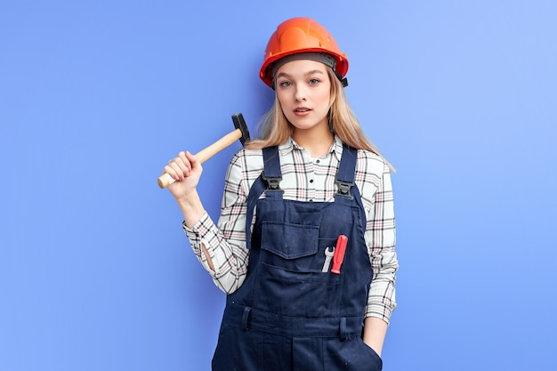 Confident architect woman holding hammer in hands ready to repair