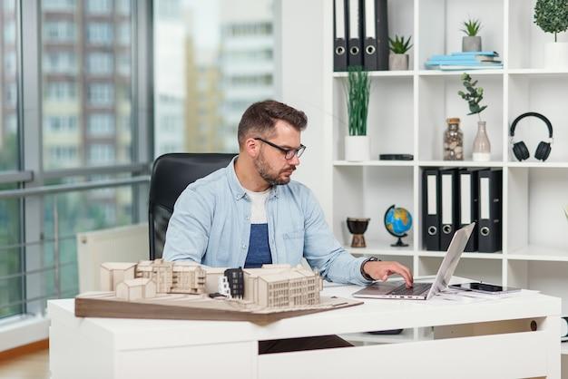 自信のある建築家がノートパソコンを持って設計局で働き、未来のモックアップの詳細を調べます