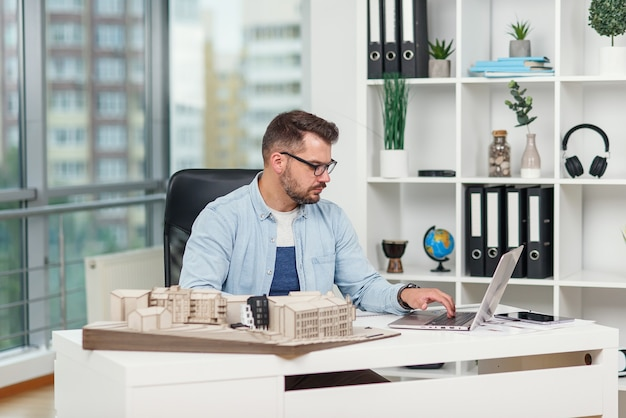Confident architect works at design bureau with laptop and examines details on mockup of future