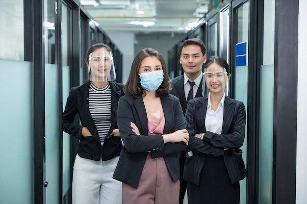 얼굴 마스크를 쓰고 자신감 아시아 비즈니스 팀, 얼굴 방패 서 사무실 복도에서 팔을 교차