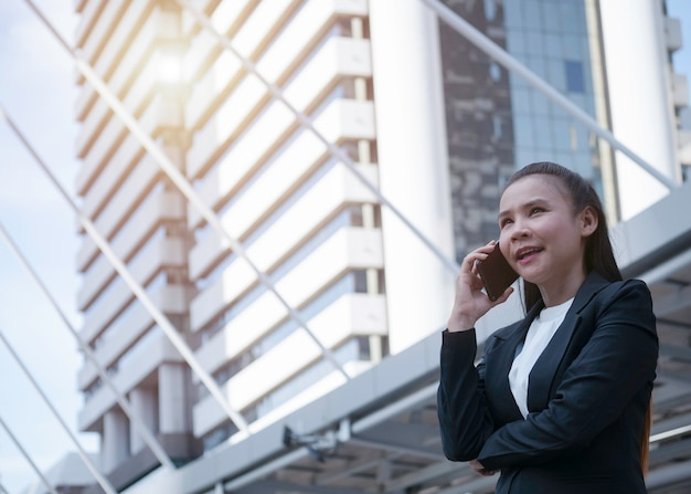 Confident asian business woman using smartphone for calling