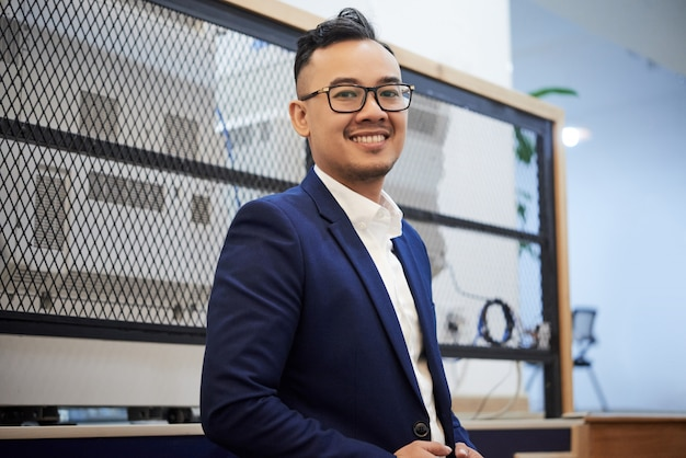 Confident asian businessman in suit posing in office