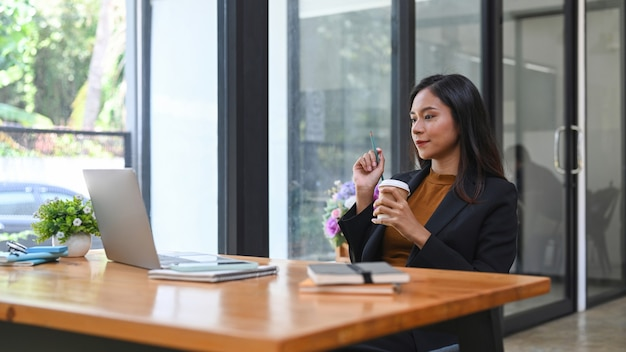 一杯のコーヒーを保持し、ラップトップコンピューターでビジネスパートナーとビデオ通話をしている自信を持ってアジアの実業家。