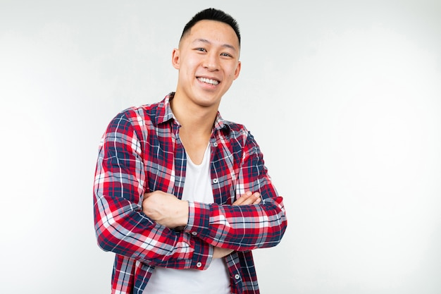 Confident asian man in a plaid shirt wide open on a white studio background with copy space