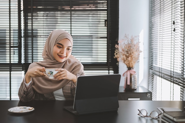 Confident asian muslim business woman brown hijab sitting and working with laptop computer at modern office.