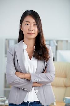 Confident asian woman in smart jacket posing in office with crossed arms