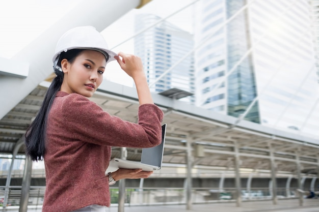 A confident asian working woman is wearing a helmet and working on a laptop while standing outdoors.