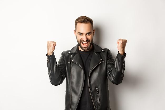 Uomo fiducioso e assertivo in giacca di pelle che fa pompare il pugno, gioia di vincere, sentirsi incoraggiato e soddisfatto