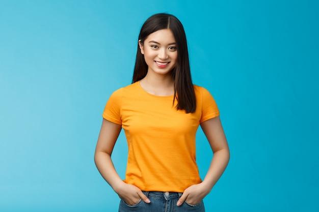 自信を持って断定的な笑顔のアジアの女性は、青い背景のカメラを見て、手をつないでジーンズのポケットは自信のある雰囲気を表現し、ポジティブな結果のスキンケア手順を楽しんで、黄色のtシャツを着てください。