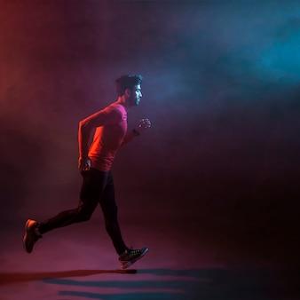 Confident athlete running in dark studio