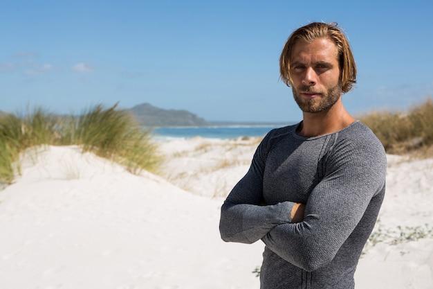 Уверенный спортсмен, стоящий на пляже против неба
