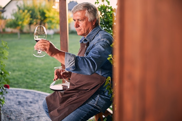 Confident attentive man in denim clothes and apron sitting in the yard with a decanter and looking at the red wine in his glass