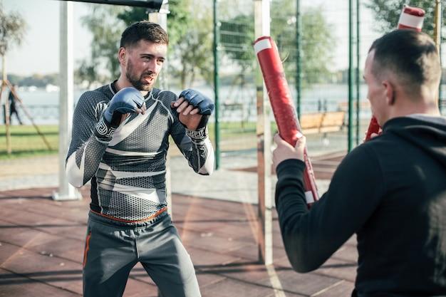 Уверенно внимательный боксер мма смотрит на боксерские клюшки в руках тренера и поднимает руки вверх