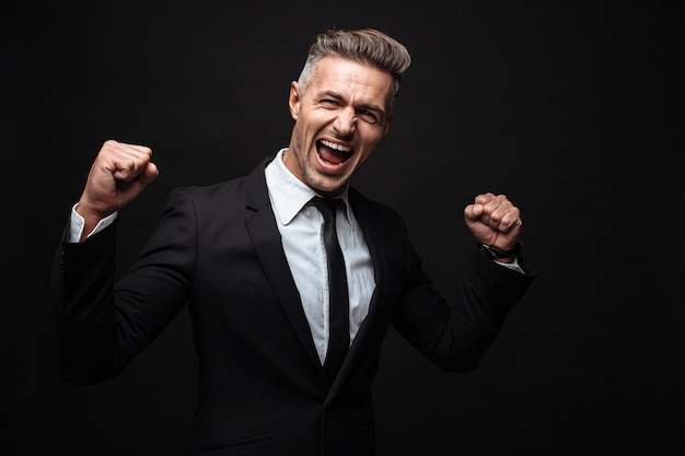 Confident attractive businessman wearing suit standing isolated over black wall, celebrating success