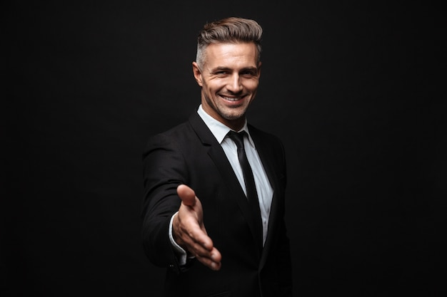 Confident attractive businessman wearing suit standing isolated over black wall, outstretched hand fir greeting