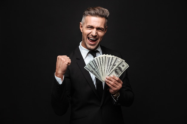 Confident attractive businessman wearing suit standing isolated over black wall, showing money banknotes, celebrating