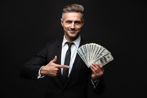 Confident attractive businessman wearing suit standing isolated over black wall, showing money banknotes, pointing finger