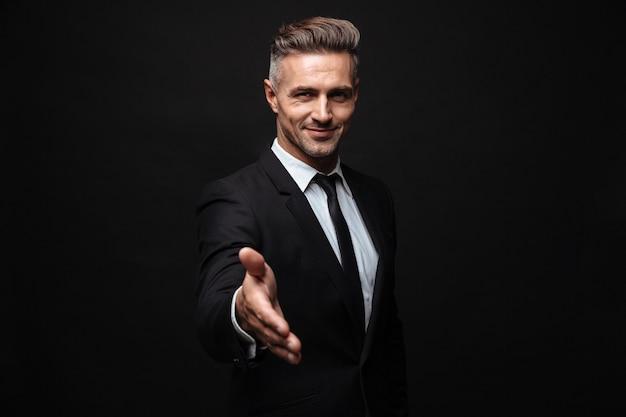自信を持って魅力的なビジネスマンが黒い壁の上に孤立して立っているスーツを着て、手を伸ばしたモミの挨拶