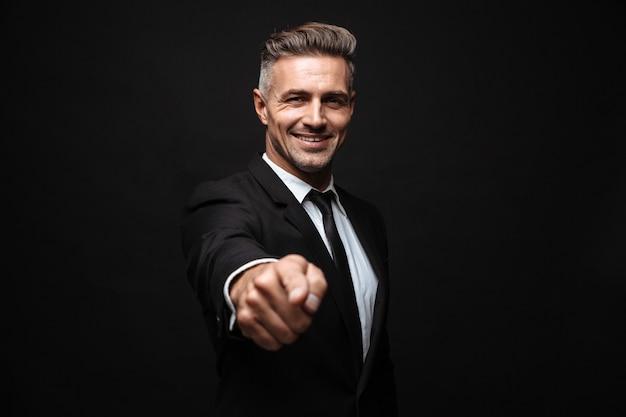 自信を持って魅力的なビジネスマンは、黒い壁の上に孤立して立っているスーツを着て、カメラに指を指しています