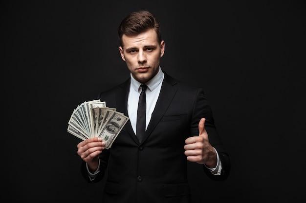 黒い壁の上に孤立して立っているスーツを着て、お金の紙幣を見せて、親指を立てて自信を持って魅力的なビジネスマン