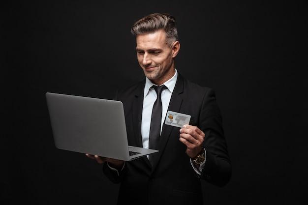 Уверенный привлекательный бизнесмен в костюме, стоящий изолированно над черной стеной, используя портативный компьютер, показывая пластиковую кредитную карту